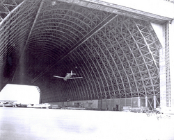 Airplane flying through open hangar bay at Naval Air Station Til